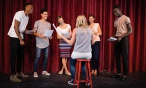 Actors reading their stage scripts during rehearsal.