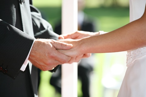 A couple holding hands at their marriage ceremony, and they are about to exchange their custom wedding vows.
