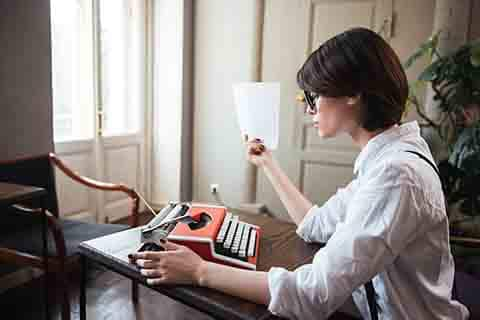 Woman author at typewriter. Will her work require editing or a rewrite?